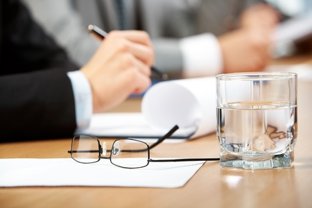 hand holding pen: Image of human hand holding pen with glass of water, eyeglasses and paper near by Stock Photo
