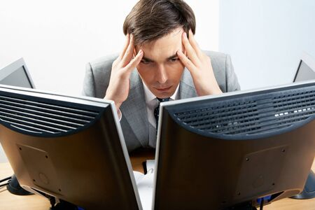 surrounded: Image of businessman touching his head while looking at monitor with tired expression Stock Photo