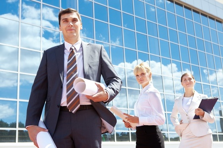Portrait of successful leader holding rolled papers with two employees behind photo