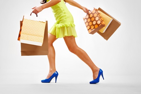 Legs of lady with colorful paper bags in move photo