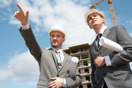 Photo of young engineer showing something to his colleague during meeting at building site photo