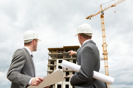 building site: Photo of young engineer showing something to his partner at building site