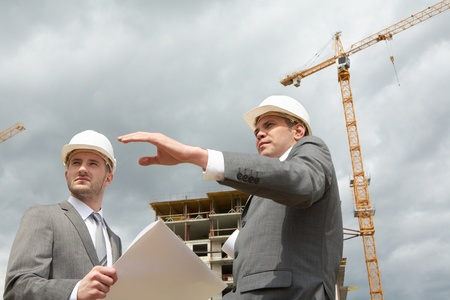 Photo of confident engineer showing something to his partner at building site photo
