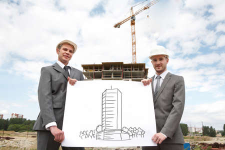 Portrait of two successful builders holding large sheet of paper with sceme of construction on it  photo