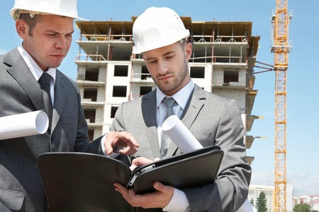 Portrait of two builders standing at building site and discussing new project held by one of them Stock Photo - 9635139