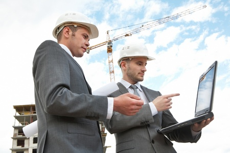 Portrait of two builders standing at building site and looking at laptop display photo