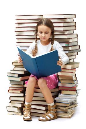 diligente: Retrato de alumno diligente sentado sobre una pila de libros y la lectura de uno de ellos Foto de archivo