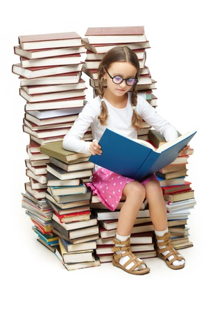 diligent: Portrait of diligent pupil sitting on pile of books and reading one of them Stock Photo