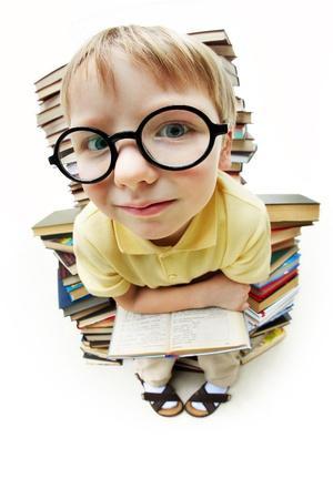 diligente: Retrato de alumno diligente sentado sobre una pila de libros y mirando la c�mara