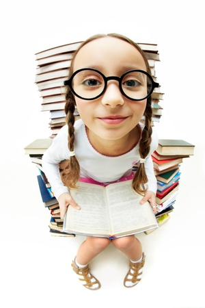 diligent: Portrait of diligent pupil sitting on pile of books and looking at camera Stock Photo