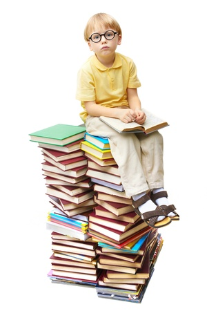 diligente: Retrato de alumno diligente sentado encima de libros y mirando la c�mara Foto de archivo