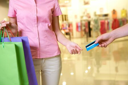 taking charge: Close-up of woman taking plastic card from male hand in the mall Stock Photo