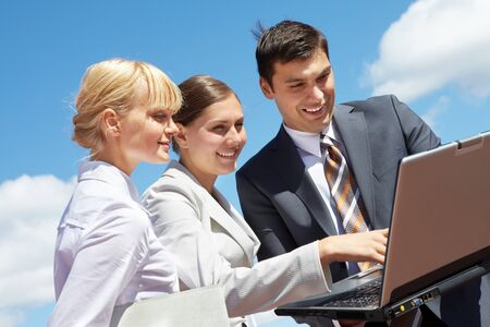 Photo of successful business partners looking at laptop during work photo