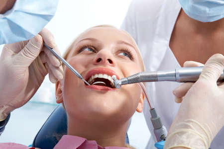 Image of young woman during inspection of oral cavity by dentist and assistant photo