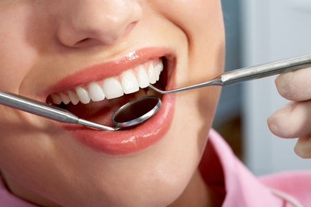 Close-up of patient�s open mouth during oral checkup with mirror and hook photo