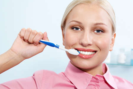 Image of happy female holding toothbrush in hand before cleaning teeth photo