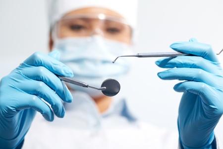 guanti infermiera: Immagine di assistente in uniforme medici titolari di odontoiatria strumenti nelle mani