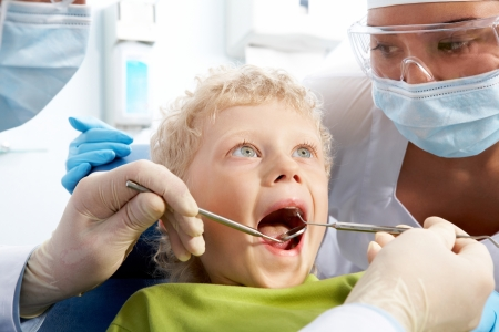 Dental inspection is being given to little boy surrounded by dentist and his assistant Stock Photo - 9675268