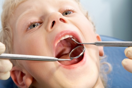 Photo of little boy having mouth checkup in dental clinic photo