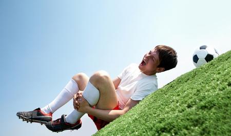 piernas hombre: Imagen de futbolista acostado y gritos de dolor