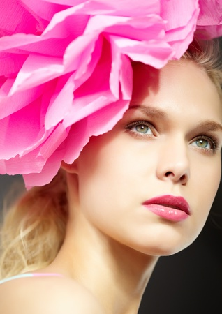 Gorgeous woman with pink flower by head photo