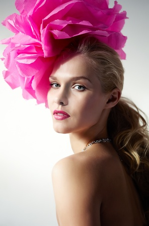 lifestyle looking lovely: Gorgeous woman with pink flower on head looking at camera Stock Photo
