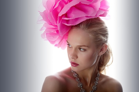 Gorgeous woman with pink flower on head looking aside photo