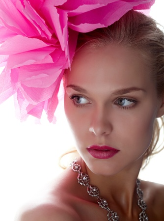 aside: Gorgeous woman with pink flower on head looking aside Stock Photo