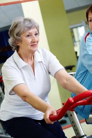 Portrait of senior female doing physical exercise on special equipment  photo