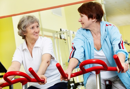Portrait of senior females doing physical exercise on special equipment in gym photo