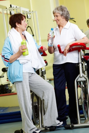 Portrait of senior females refreshing after workout in gym photo