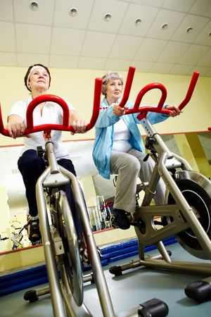 Portrait of senior females doing physical exercise on special equipment  photo