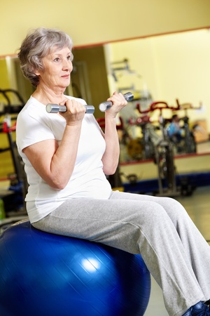 Portrait of aged woman doing physical exercise with barbells while sitting on blue ball  photo