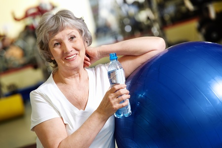 athletic activity: Portrait of aged woman with bottle of water by blue ball