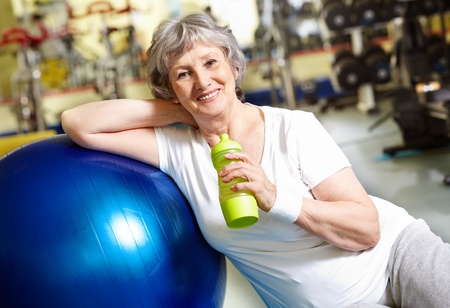 water sports: Portrait of aged woman with bottle of water by blue ball