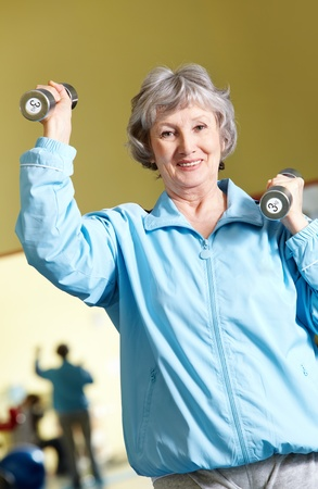 Portrait of aged woman doing physical exercise with barbells photo
