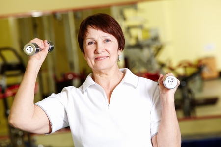 Portrait of aged woman doing physical exercise with barbells Stock Photo - 9675252