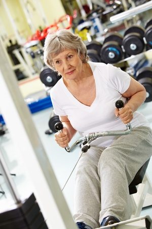 pumping: Photo of active woman pumping muscles on special equipment