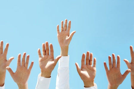 manos levantadas al cielo: Primer plano de varias manos humanas contra claro cielo azul