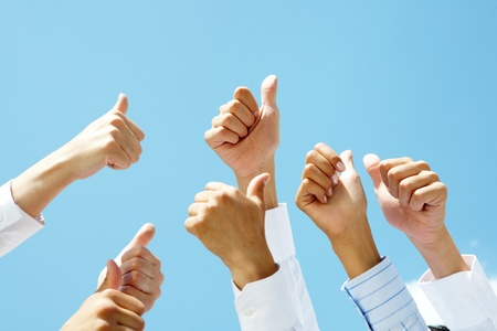 Image of several human hands showing thumbs up against clear blue sky photo