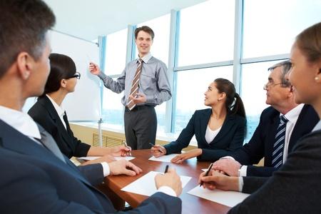 Foto van een succesvolle zakenman, het lezen van les aan zijn collega's bij presentatie van het nieuwe project