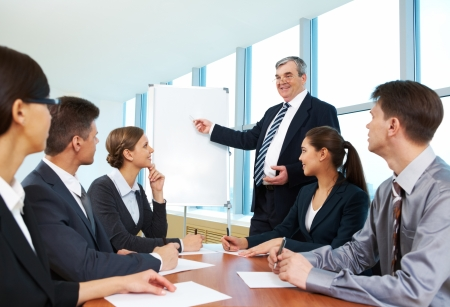 Smart and confident boss pointing at whiteboard and looking at managers during presentation photo