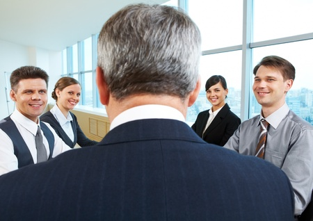 Rear view of aged businessman making report to partners at conference photo