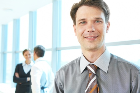 Portrait of confident boss looking at camera on the background of talking people photo