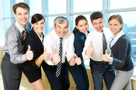 Portrait of happy co-workers looking at camera with smiles and showing sign of okay Stock Photo - 9675382