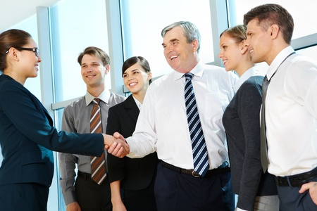 Photo of successful associates handshaking after striking deal with partners near by Stock Photo - 9675267