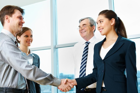 Photo of successful partners handshaking after signing agreement at meeting photo