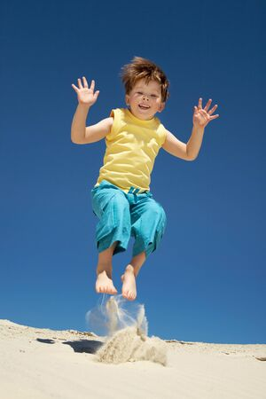 Happy boy jumping on sand and looking at camera with smile during summer vacations photo