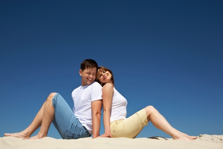 hot wife: Portrait of relaxing couple sitting back to back on sandy beach against blue sky