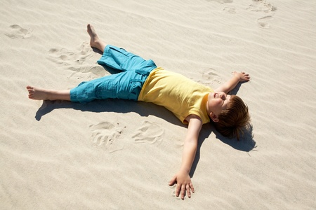 Above view of happy boy lying on sand and enjoying sunlight photo